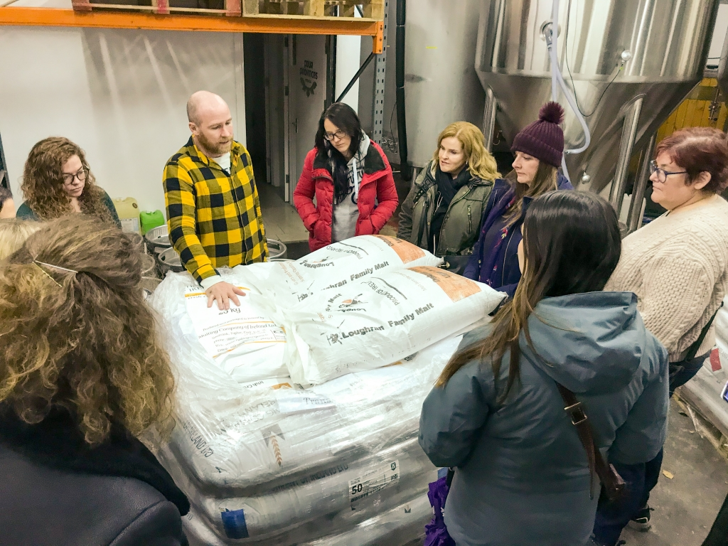 women visiting brewery looking at bags of grain
