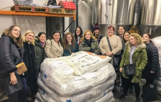 group around bags of malt and grain