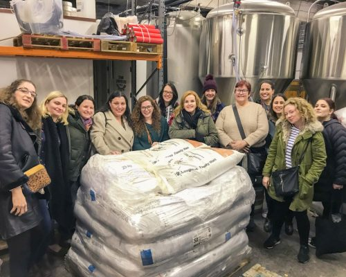 women surrounding bags of grain at brewery